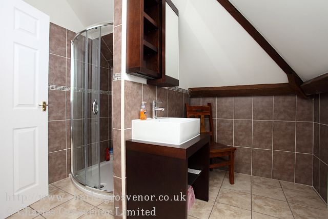 The photograph is showing the bathroom split into tow areas with tiling to the floor and walls.