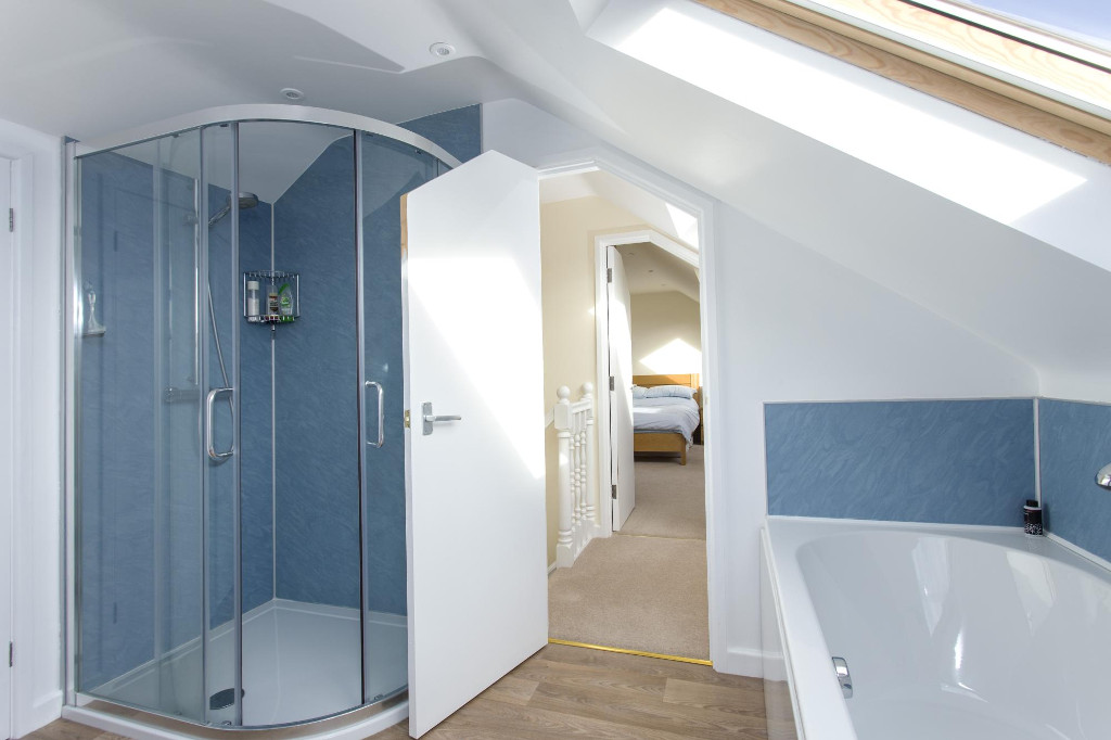 Large shower room with bath and Velux rooflight